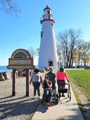 3 women and one man in front of a light house.jpg