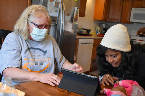woman helping another woman on an ipad