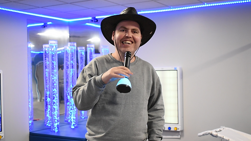 man singing into microphone wearing a cowboy hat