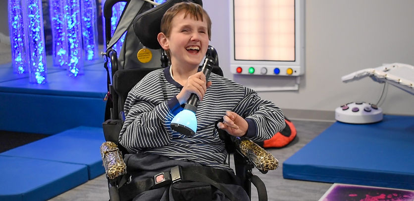 man in a wheelchait singing into a microhphone