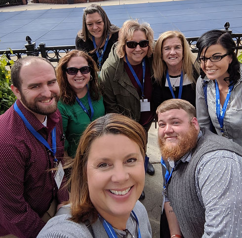 multiple staff members taking a selfie, all wearing blue landyards