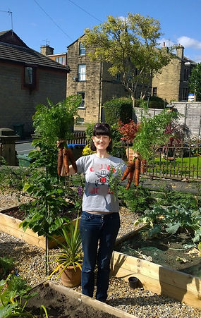 A happy smiling lady stands in her yorkshire garden proudly holding organic carrots