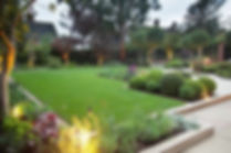 A mainicured lawn with beautiful flower beds and topiary