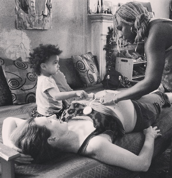 A home birth Midwife offering care while including the help of a toddler child.