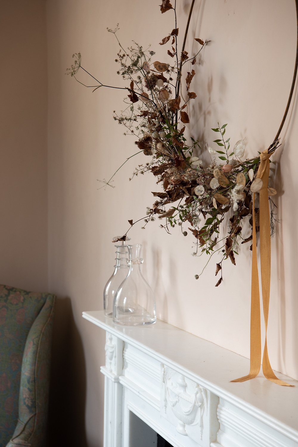 a wreath made with foraged seed heads and twigs hanging above the fire place