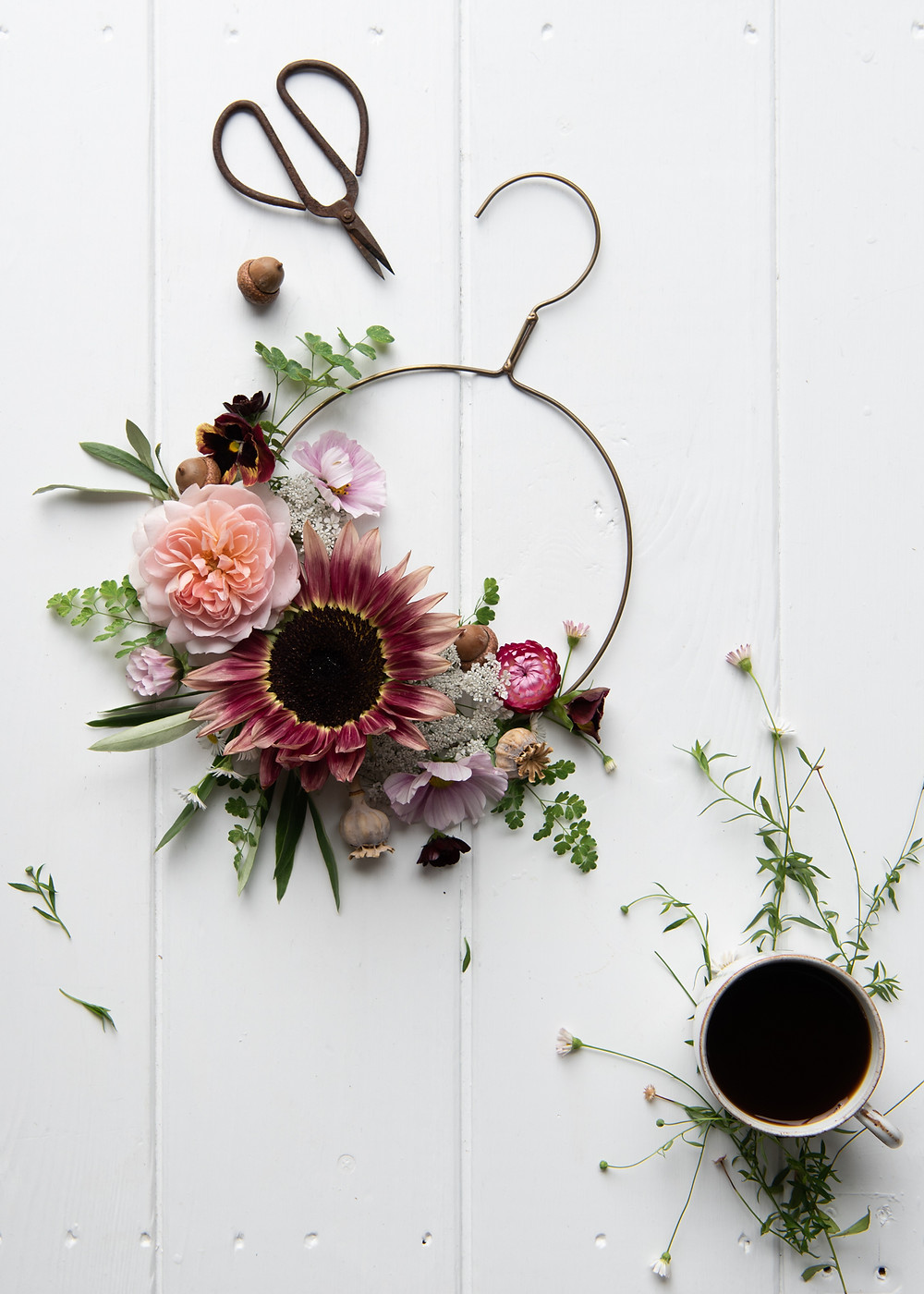 autumn flowers on a brass hoop laid on a white table top