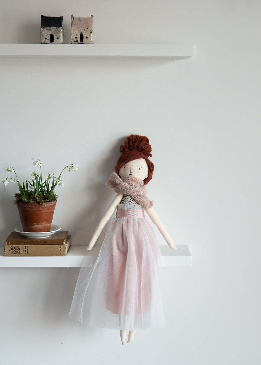 A handmade cloth doll with red wool hair and a tulle skirt sitting on a shelf