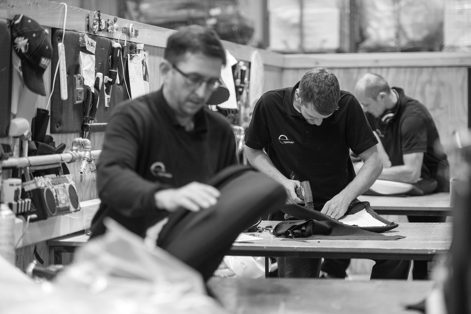 Production line of craftsman working on bespoke chairs.