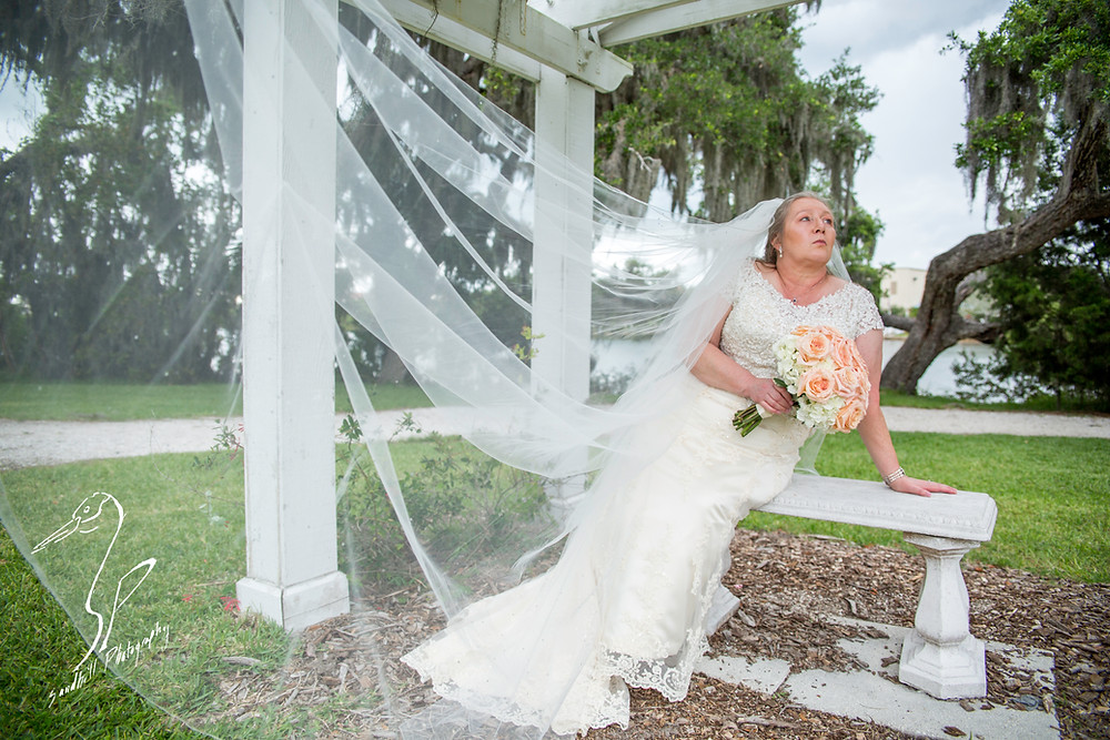 Rainy Day Wedding Photography Sarasota, Bridal Portrait with bride sitting on a bench and her cathedral veil blowing in the wind