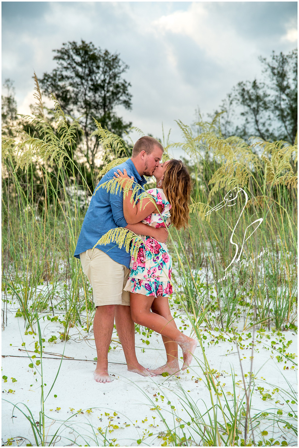 Bradenton Beach Engagement Photography, an engaged couple embrace and share a private kiss in the sand dunes, by Sandhill Photography