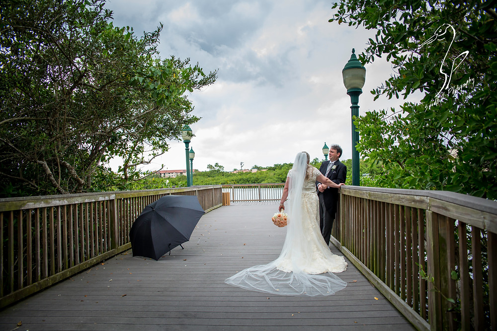 Rainy Day Wedding Photography Sarasota, bride and groom on a bridge with the umbrella beside them