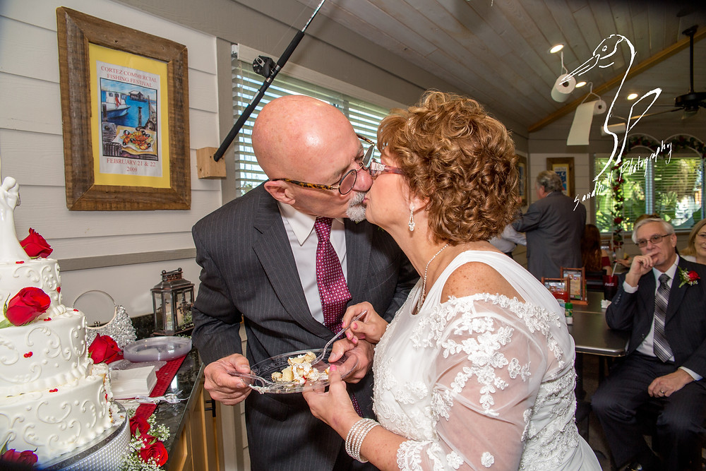 Anna Maria Oyster Bar Wedding Photography Cake cutting kiss