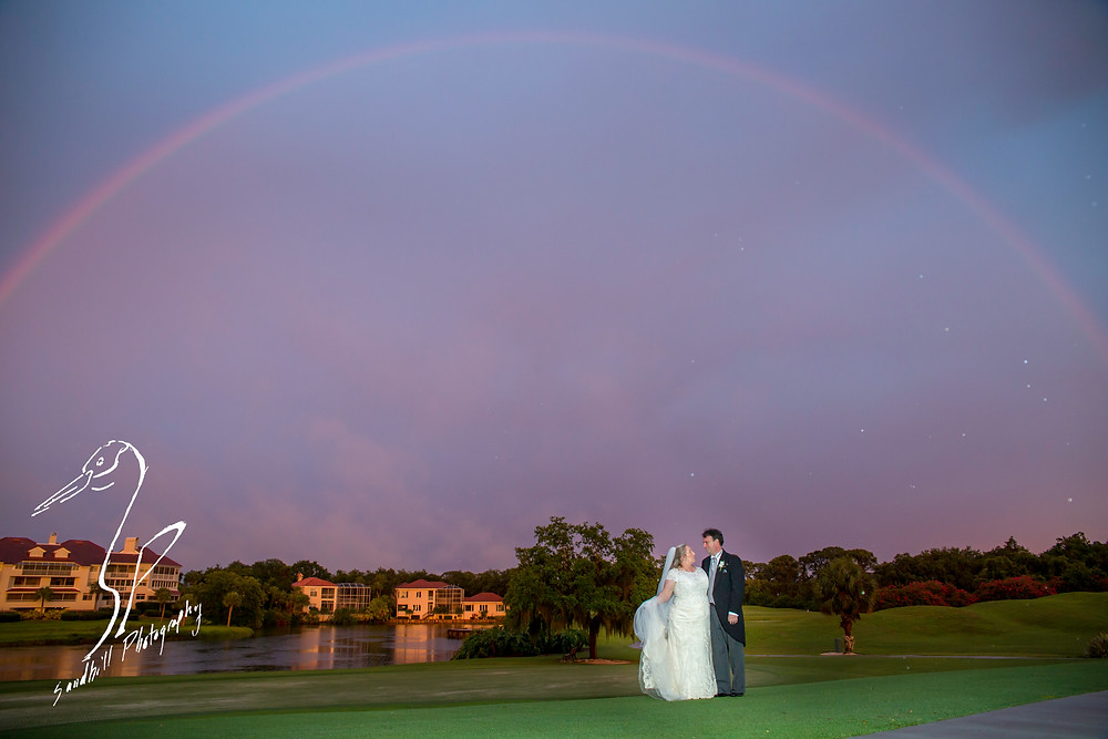 Rainy Day Wedding Photography Sarasota, Bride and groom standing beneath a full rainbow at sunset
