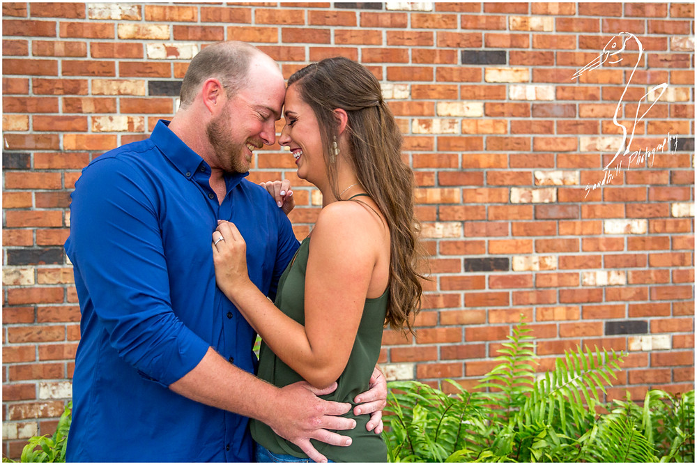 Downtown Bradenton Engagement Photography an engaged couple lean their heads together, laughing as they embrace by an exposed brick wall