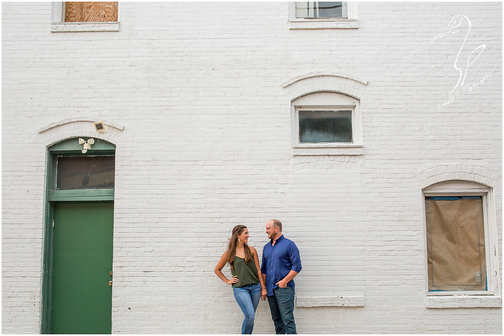 Downtown Bradenton Engagement Photography, urban imagery of an engaged couple standing in front of a large white brick wall on Old Main St.
