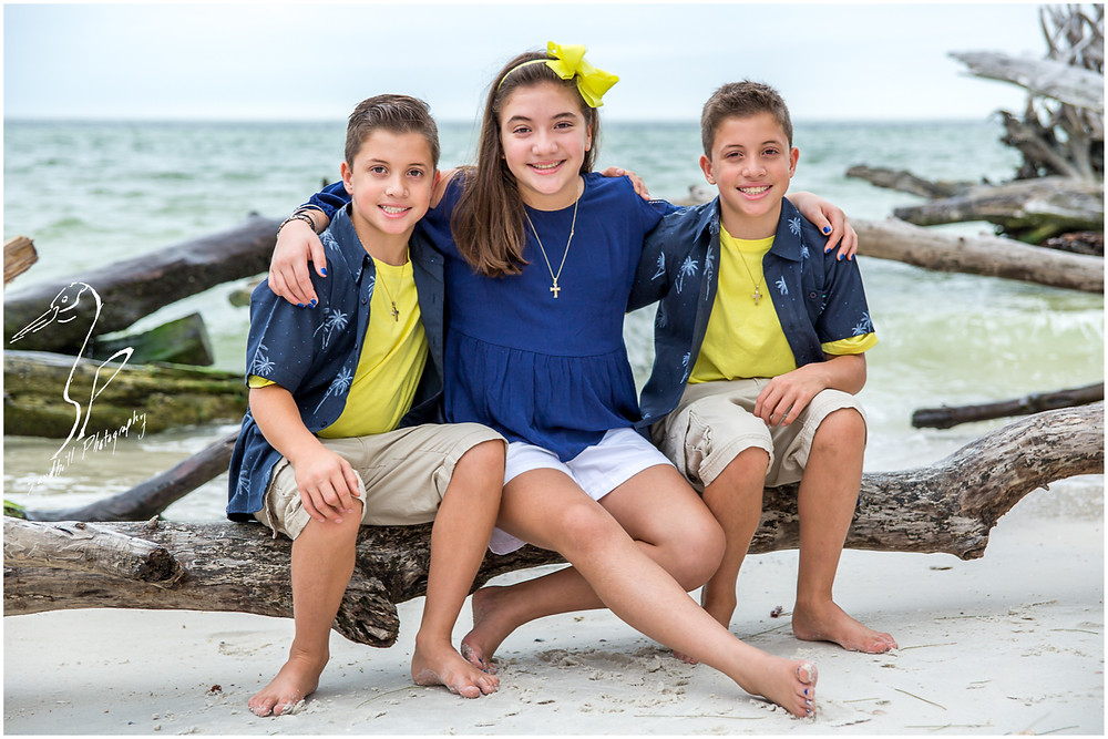 Longboat Key Family Photographer, 3 siblings sit on a driftwood log at Beer Can Island, taken by Sandhill Photography