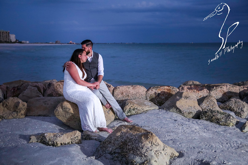 Treasure Island Wedding, Wedding portrait, groom kisses brides forehead sitting on the rocks at dusk