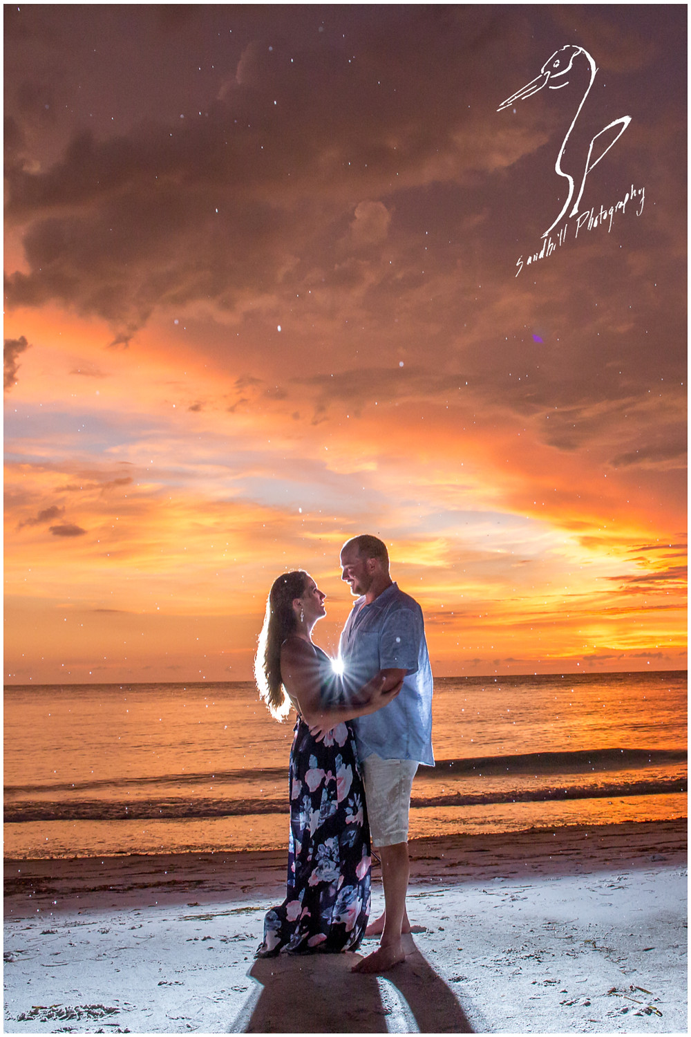 Beer Can Island Engagement Photography, back lit picture with a starburst between a couple looking into each other's eyes on Longboat Key