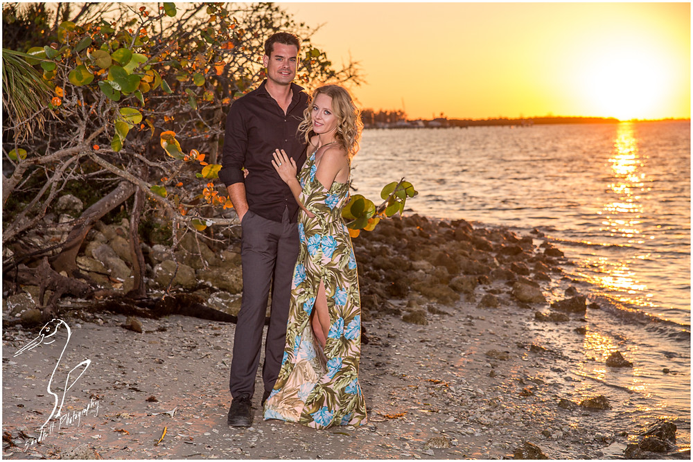 DeSoto National Memorial Photography, an engaged couple stand on the shores of the manatee river at sunset