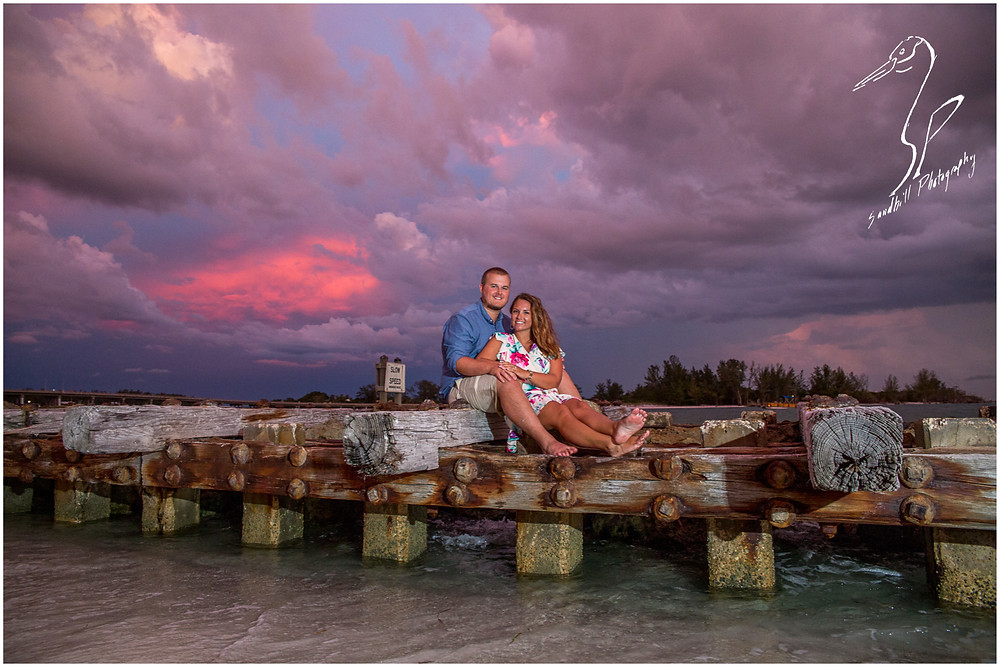 Bradenton Beach Engagement Photography, a couple sits on a jetty at sunset with purple clouds behind them