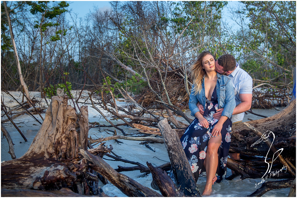 Longboat Key Engagement Photographer,a women sits on a drift wood log at the beach as her fiance kisses his neck