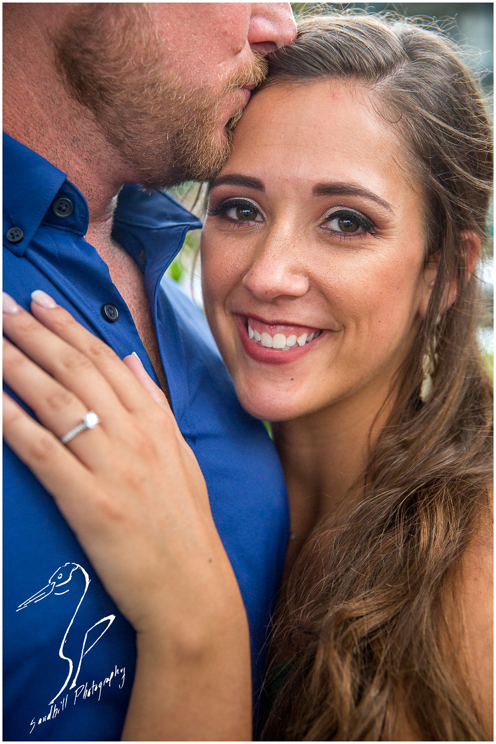 Downtown Bradenton Engagement Photography, a woman smiles at the camera as her fiance kisses her forehead, with her engagement ring in the foreground
