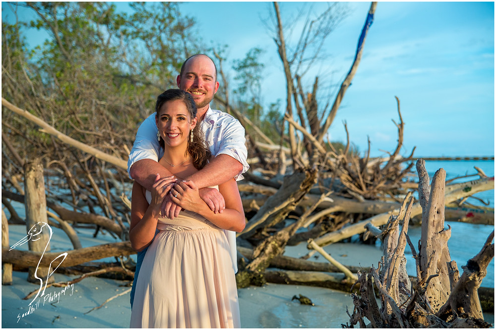 Beer Can Island Engagement Photography, engaged couple with arms entwined on a drift wood covered beach