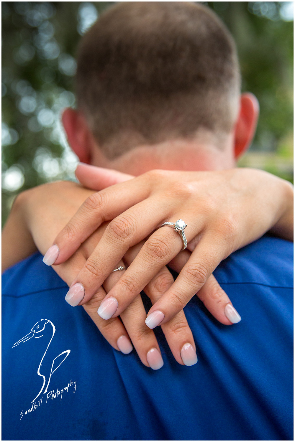 Downtown Bradenton Engagement Photography, detail picture of engagement ring on the hand of a woman embracing her fiance.