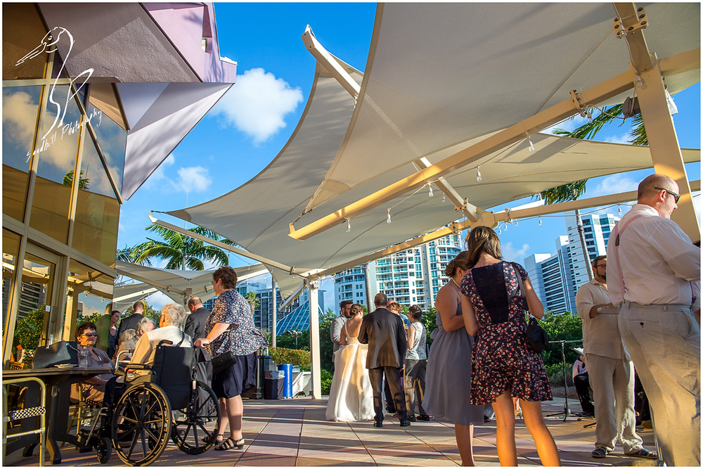 Van Wezel Wedding Photography, guests mingle on the terrace during the cocktail hour, downtown Sarasota in the background.