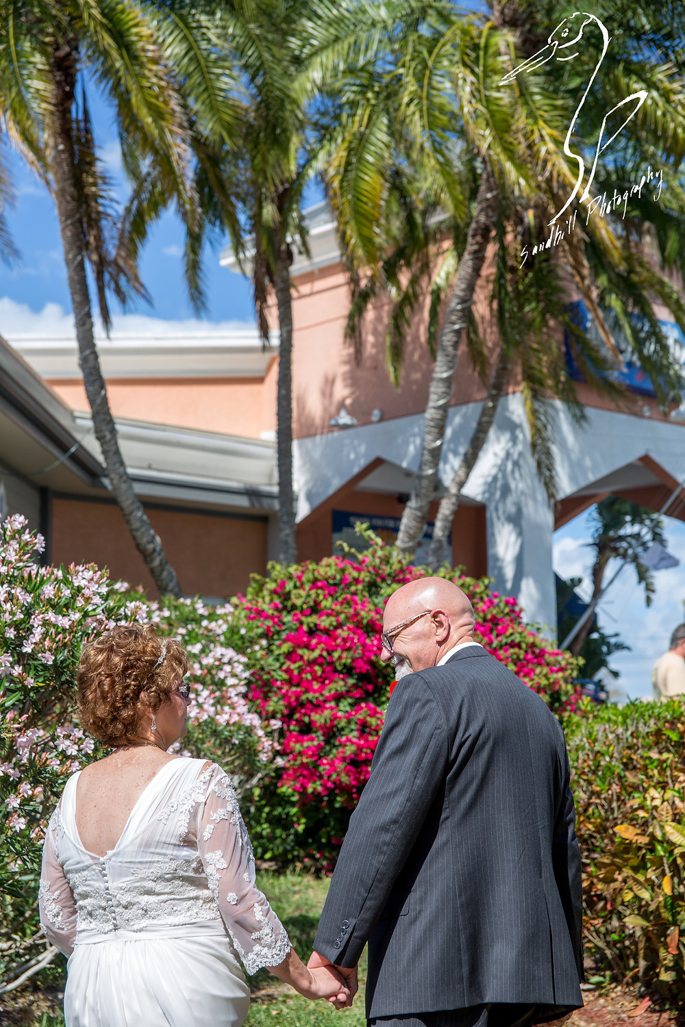 Anna Maria Oyster Bar Wedding Photography Bride Groom  Palm Trees pink flowers walking outside sunny