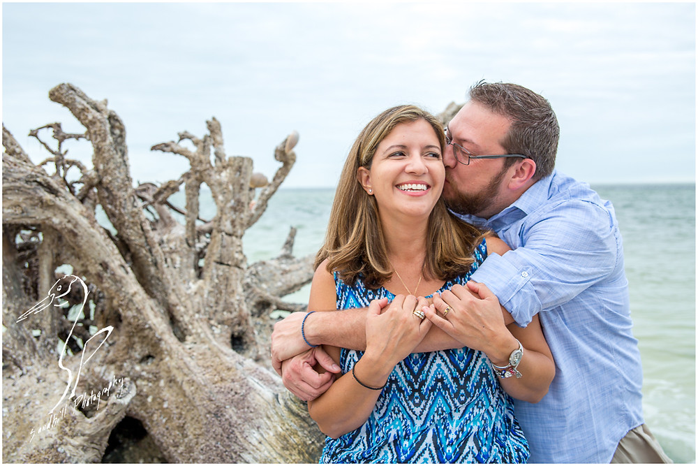 Longboat Key Family Photographer, husband and wife share a sweet kiss on the beach by the driftwood Sandhill Photography