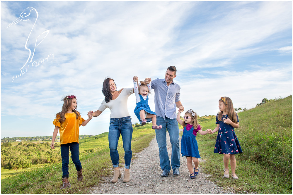 Bradenton Family Photographer | Top 10 tips for Pictures with Kids, family holding hands and walking down a hill