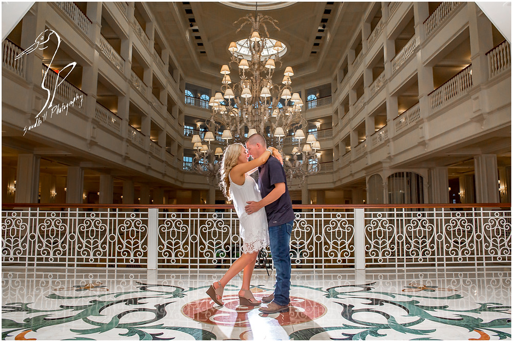 Disney's Grand Floridian Engagement Session, backlit photograph of engaged couple in front for the giant chandelier.