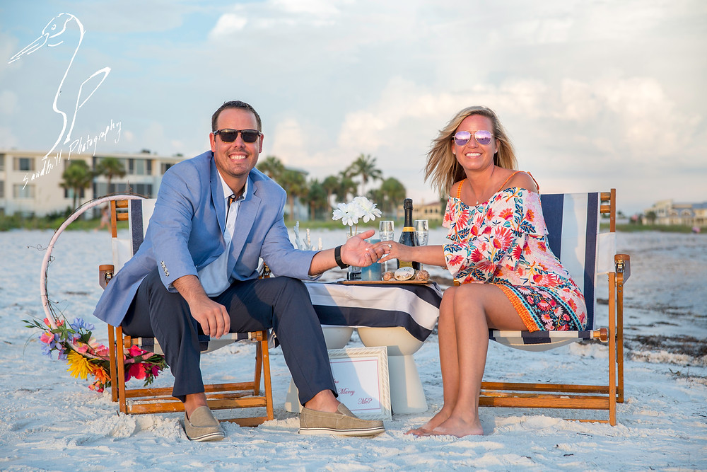 Longboat Key Surprise Proposal couple sitting in beach chairs holding hands