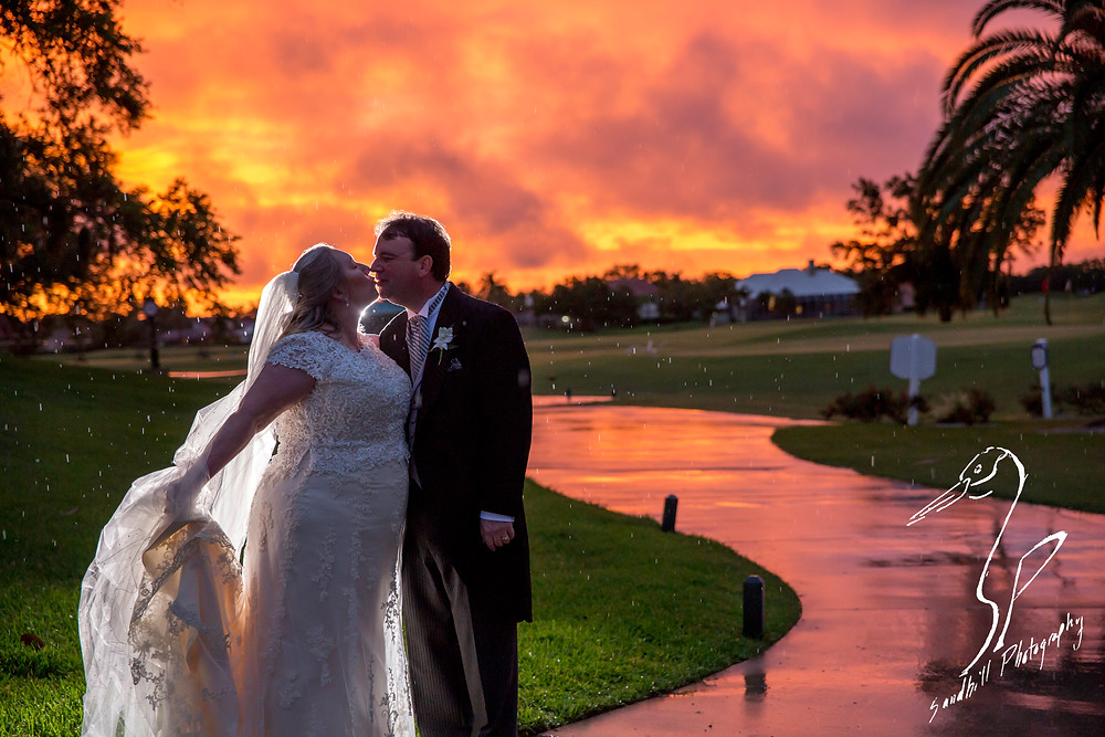 Rainy Day Wedding Photography Sarasota, back lit photography with the bride and groom silhouetted against the sunset in the rain