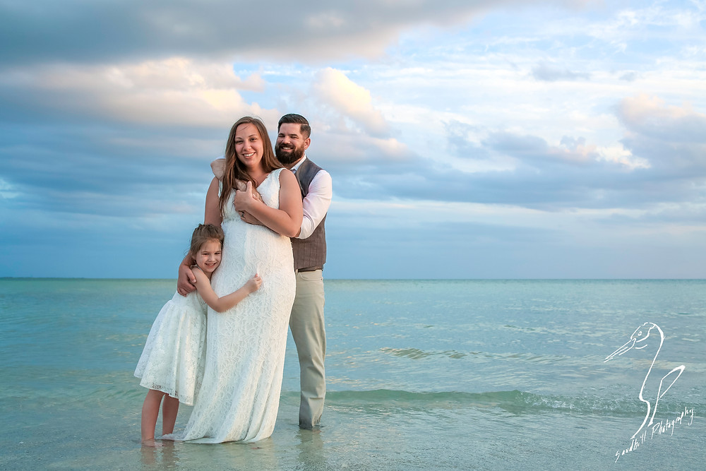 Treasure Island Wedding, Bride and Groom embracing with Flower girl in the water