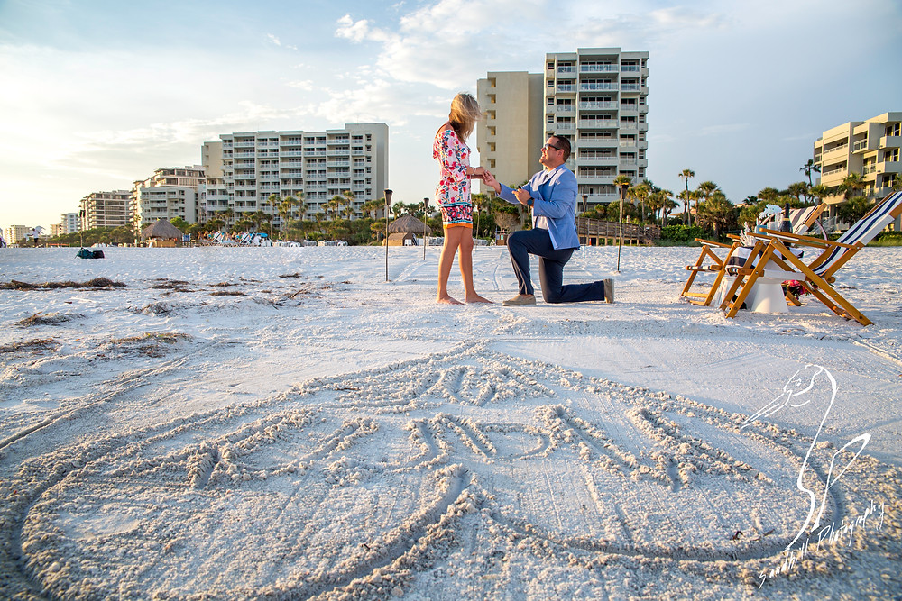 Longboat Key Surprise Proposal groom is on one knee proposing to his fiance, taken by Sandhill Photography