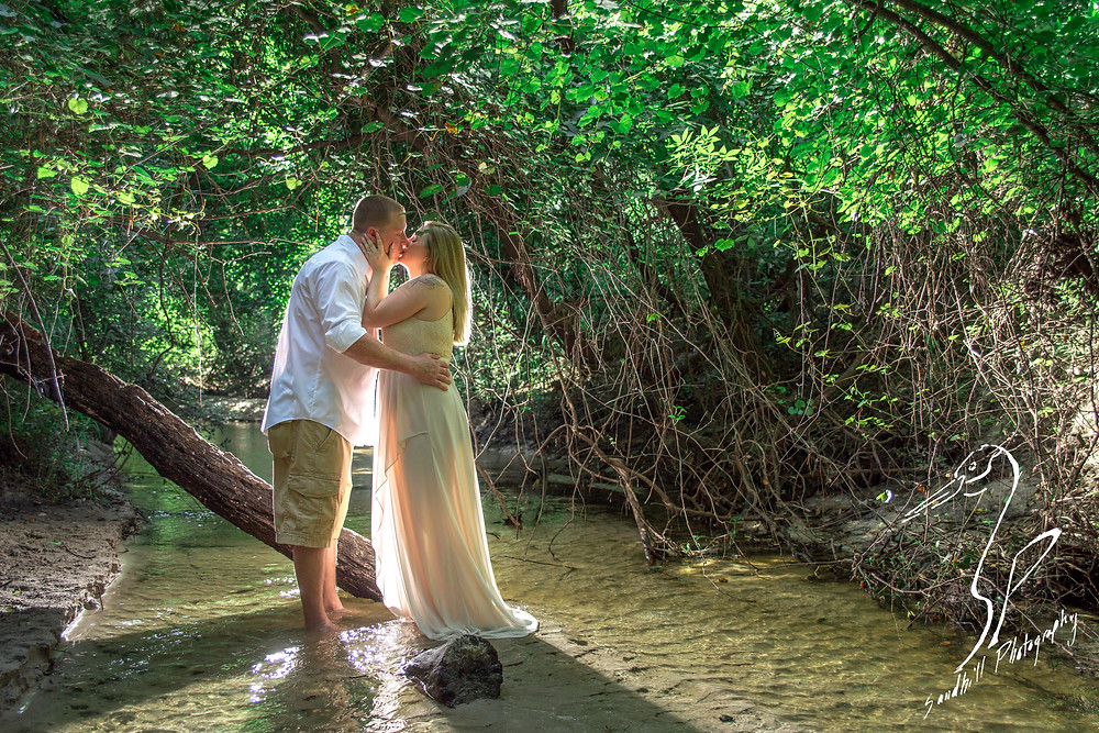 Rye Preserve Engagement in Bradenton, couple kissing while standing in a creek. back lit photography