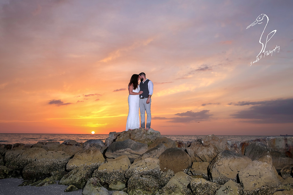 Treasure Island Wedding, Bridal Portrait, bride and groom embracing on the rocks at sunset
