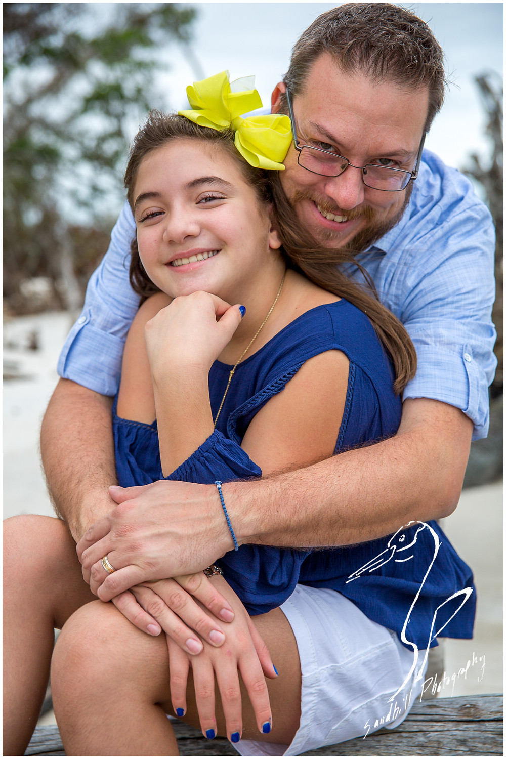 Longboat Key Family Photographer, a father embraces his daughter for a portrait taken by Sandhill Photography