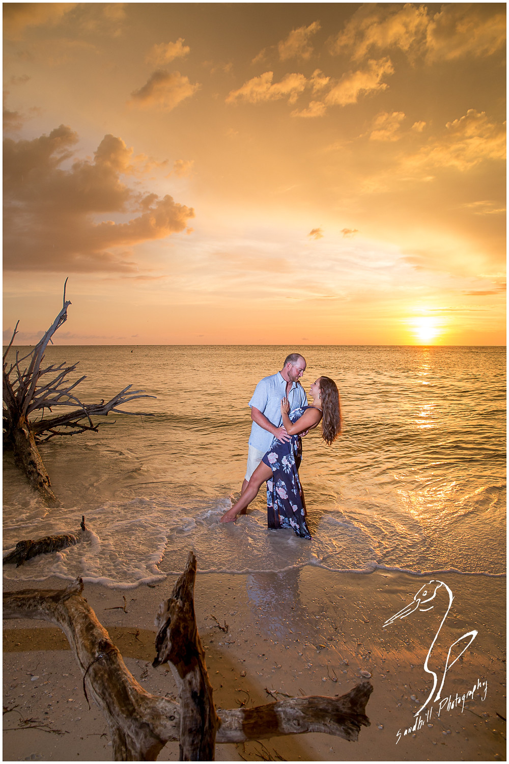 Beer Can Island Engagement Photography, couple stand in the water at sunset as he dips her