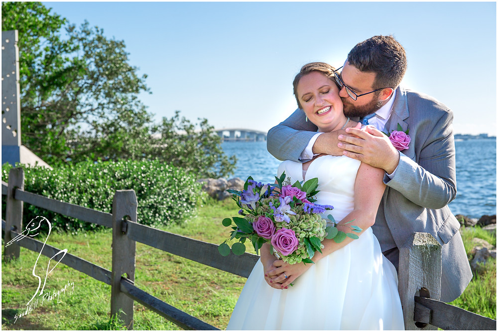 Van Wezel Wedding Photography, Bride and groom lean against a fence as he wraps his arms around her, Sarasota Bay