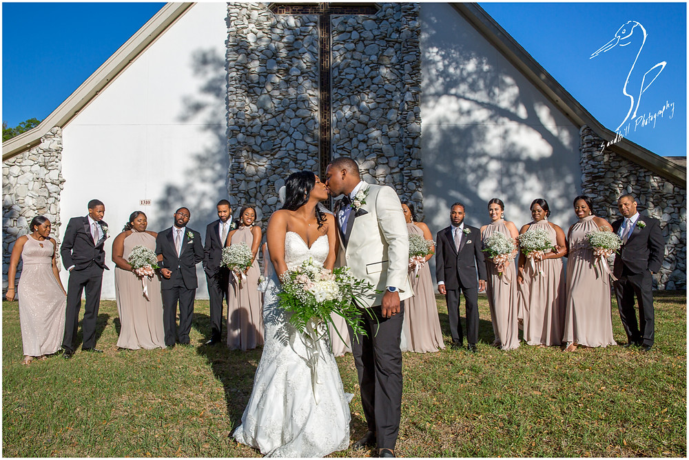 Bradenton Wedding Photographer, The bride and groom kiss as their wedding party watches from behind them in front of United First Methodist Church of Seffner
