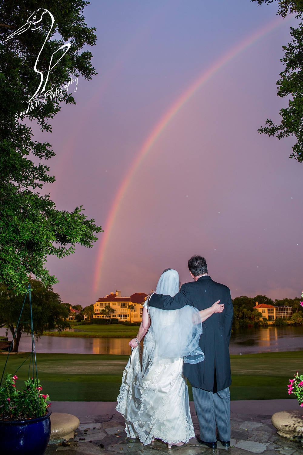 Rainy Day Wedding Photography Sarasota, Bride and groom standing beneath a rainbow at sunset