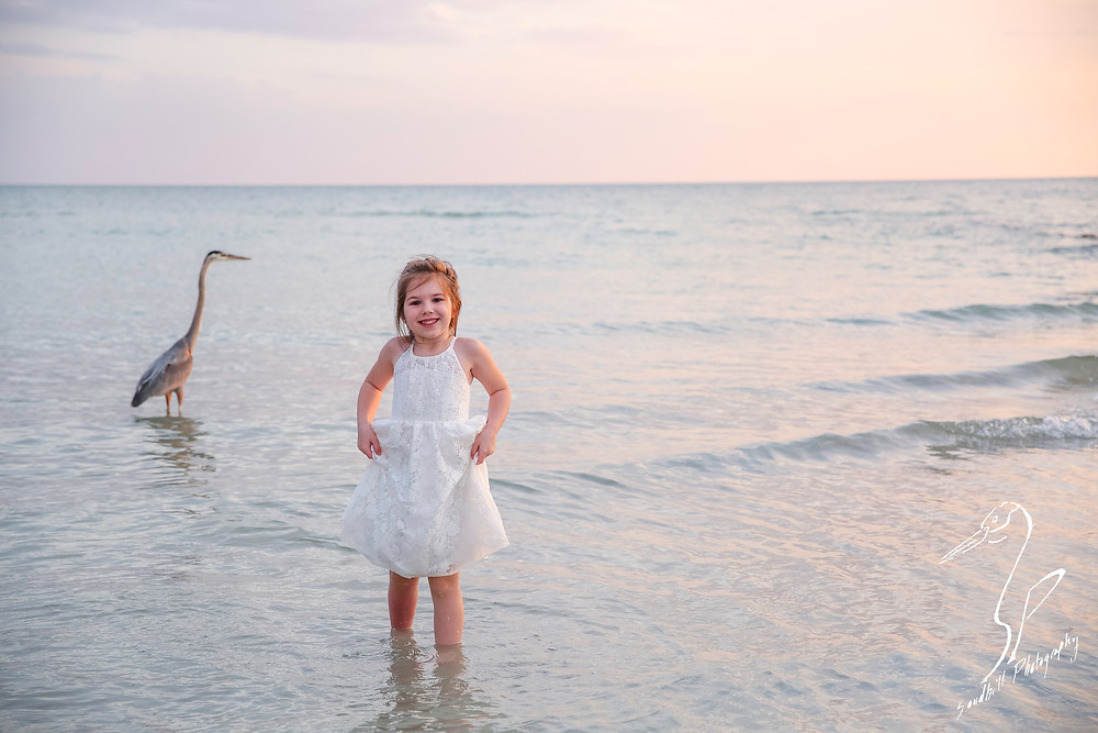 Bradenton Family Photographer | Top 10 tips for Pictures with Kids, girl lifts her dress while standing in the water