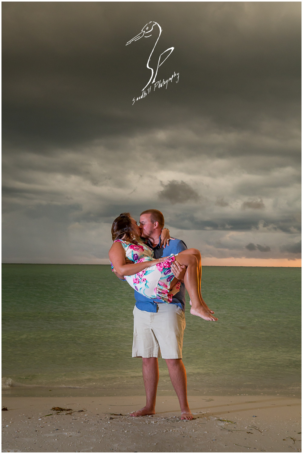 Bradenton Beach Engagement Photography, a man carries his fiance in his arms at sunset as a storm rolls into the background