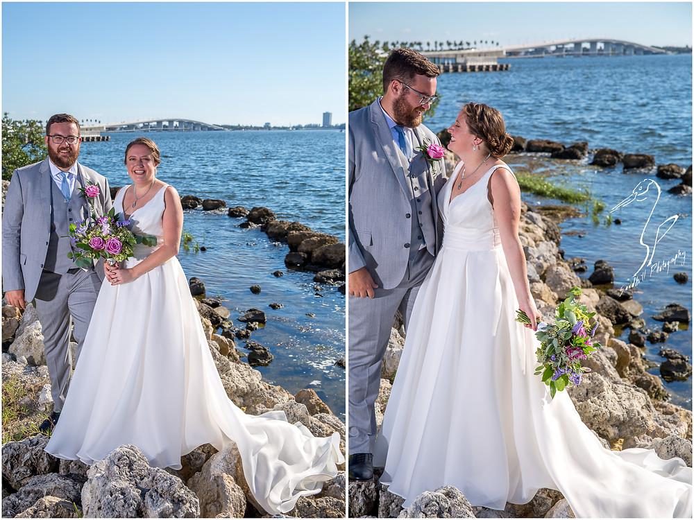 Van Wezel Wedding Photography, Bridal Portraits of bride and groom standing on the rocks beside Sarasota Bay