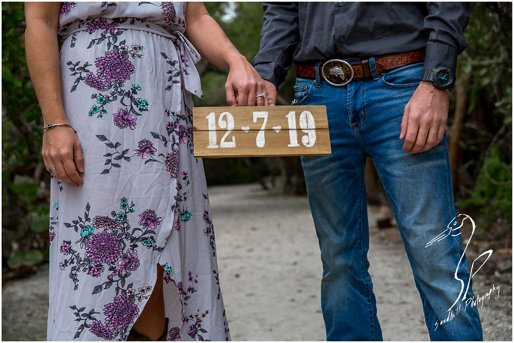 Bradenton Engagement Photographer, couple holds rustic save the date sign at their engagement session