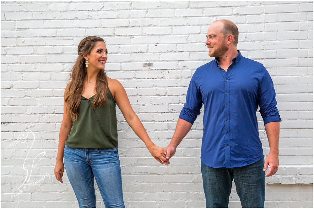 Downtown Bradenton Engagement Photography, an engaged couple in an urban setting hold hands and look at each other against a white brick wall