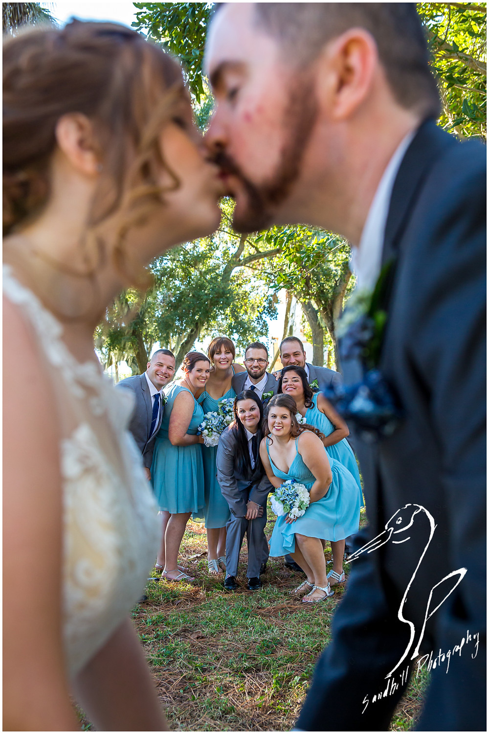 Sarasota the wedding party smiling behind a bride and groom as they kiss. unique wedding picture by Sandhill Photography